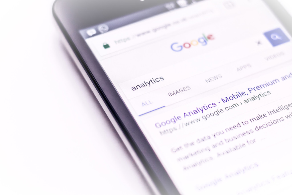 Photo of a phone with a screenshot of a search for Google Analytics