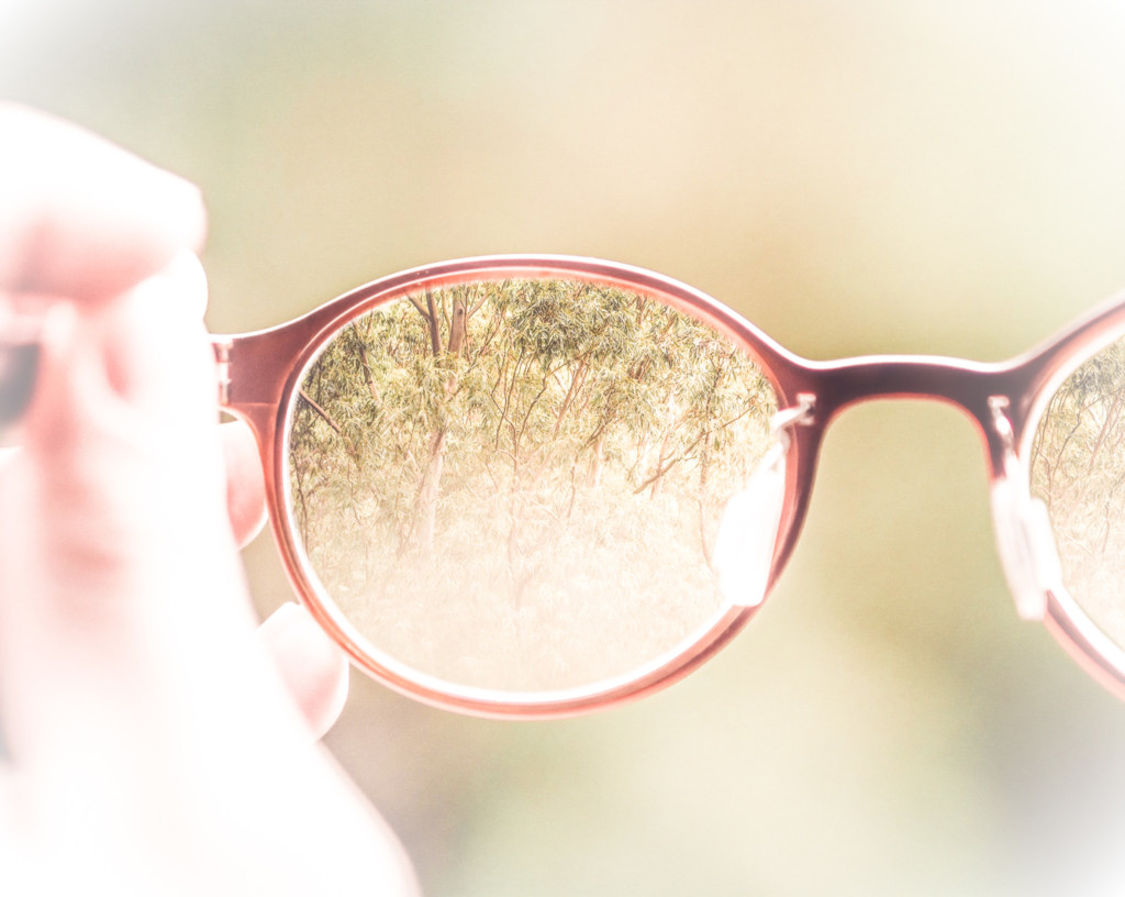 Photo of a person holding up a pair of glasses. The background is clear through the lenses.