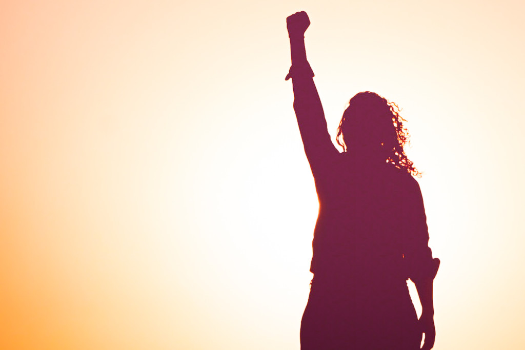 Photo of a woman standing with her fist triumphantly in the air.