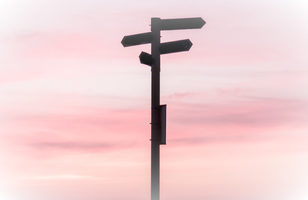 Photo of a series of directional signs on a post against a sunset sky.