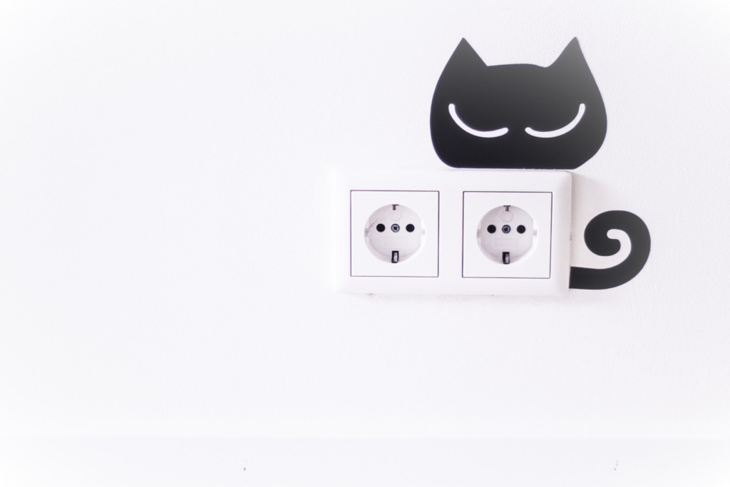 Photo of a pair of wall outlets with a cat vinyl decoration.