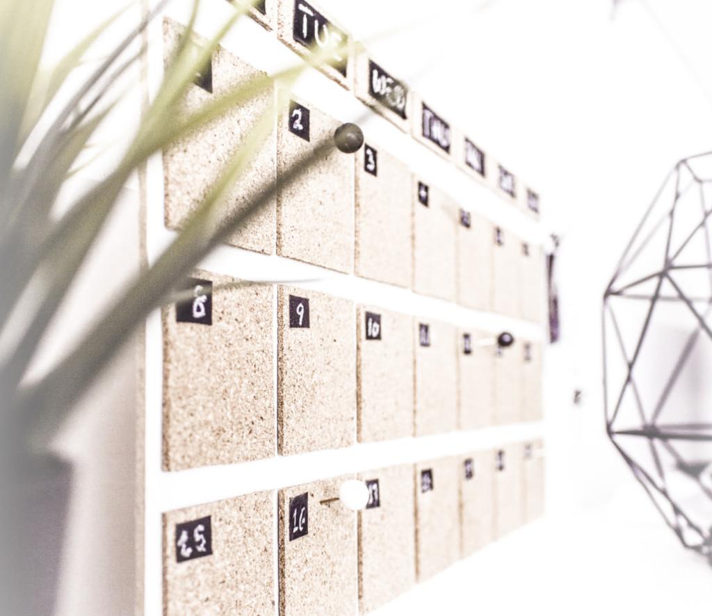 Photo of a corkboard calendar on a modern desk.
